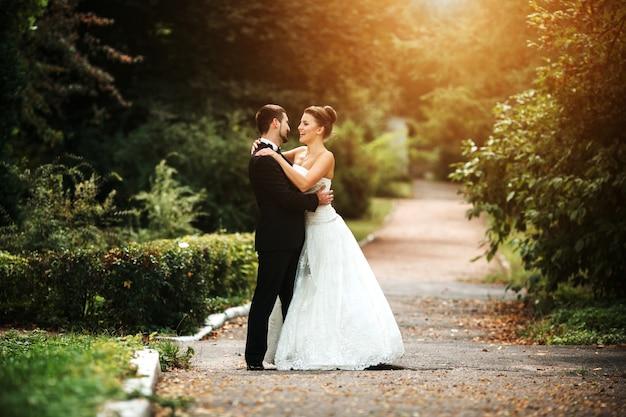 Sorridente sposi in posa al tramonto Foto Gratuite