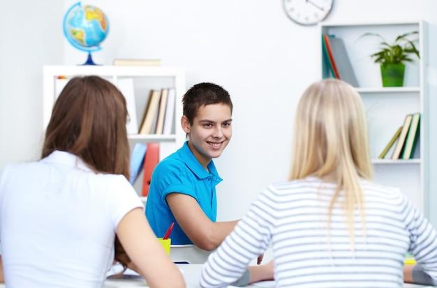 Sorridente studente guardando i suoi compagni di classe Foto Gratuite