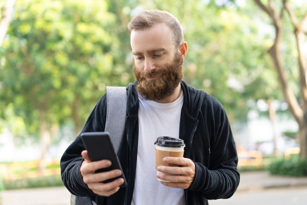Sorridente uomo barbuto che cammina in città e utilizzando smartphone Foto Gratuite
