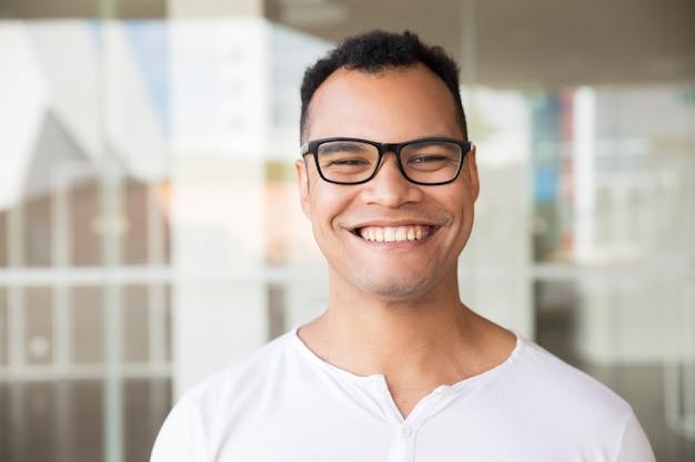 Sorridente uomo in piedi a edificio, guardando dritto fotocamera Foto Gratuite