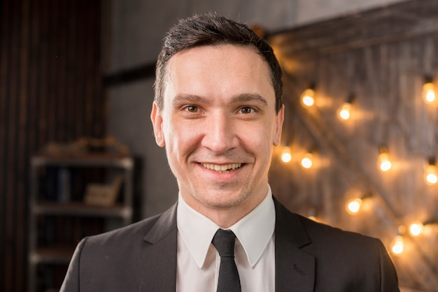 Sorridente uomo vestito guardando la fotocamera Foto Gratuite