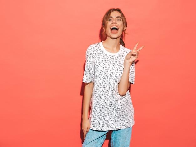 Sorridere femminile positivo modello divertente che posa vicino alla parete rosa in studio. mostra il segno di pace Foto Gratuite