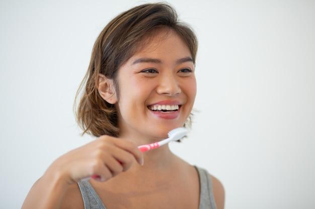 Sorridere i denti di spazzolatura della donna asiatica graziosa Foto Gratuite