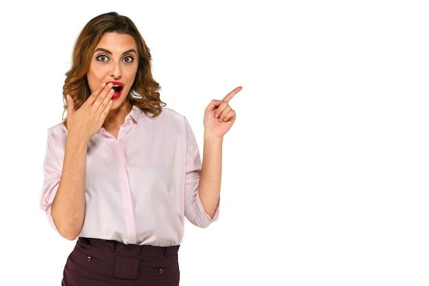 Sorridere uomo d'affari sorpreso che presenta lo spazio della copia, coprente la sua bocca di dito Foto Gratuite