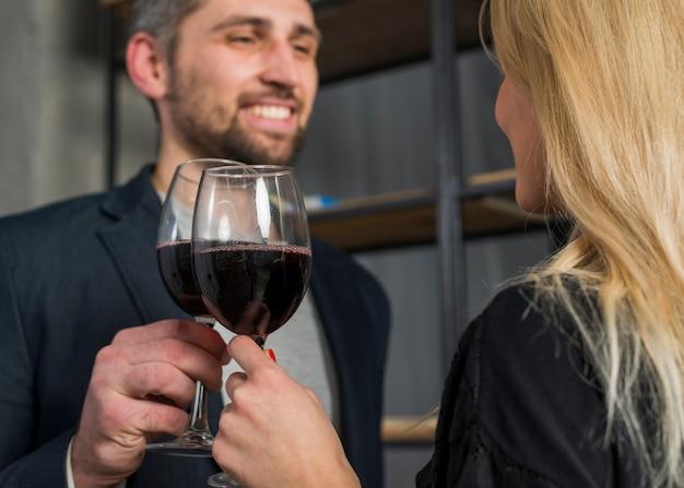 Sorridere vetri maschii e femminili di clanging della bevanda nella sala Foto Gratuite