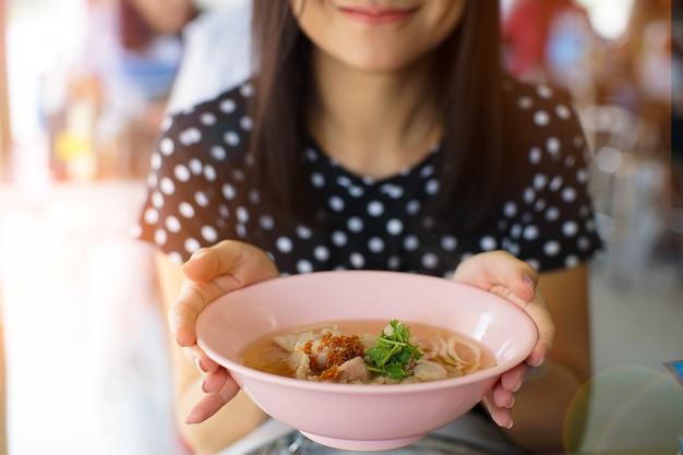 Sorridi la donna asiatica che tiene una ciotola di tagliatella in ristorante Foto Premium