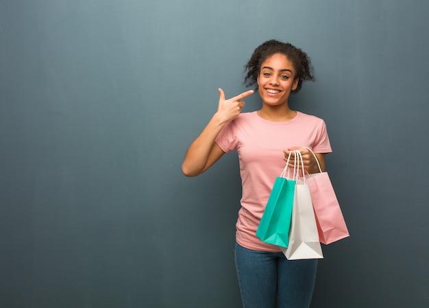 Sorrisi di giovane donna di colore, indicando la bocca. ha in mano un carrello. Foto Premium