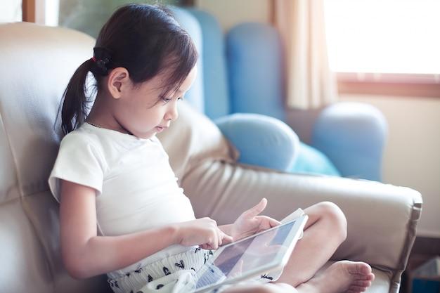 Sorriso asiatico della bambina che si siede sul sofà facendo uso dello sguardo del cuscinetto digitale della compressa nel salone a casa. Foto Premium