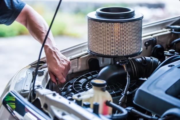 Sostituzione del filtro dell'aria dell'automobile se si guida in un'area polverosa, è necessario sostituirlo più spesso, con il concetto di manutenzione della vettura. Foto Premium