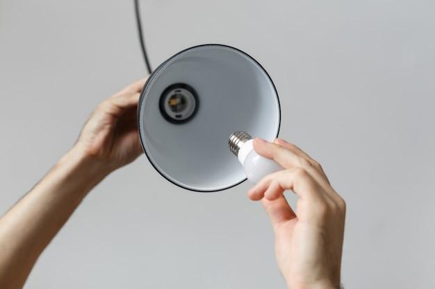 Sostituzione della lampadina per lampadina a led nella lampada da terra in colore nero. su sfondo grigio chiaro Foto Premium