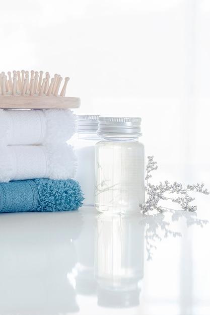 Spa set con pila di asciugamani puliti, bottiglia di olio, pettine in legno e fiori Foto Premium