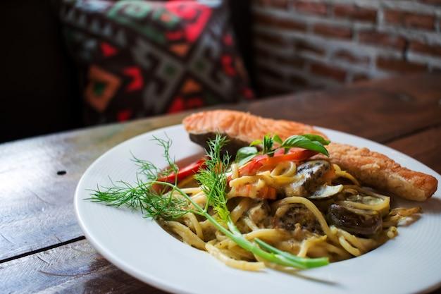 Spaghetti al curry verde e un grosso pezzo di salmone. Foto Premium