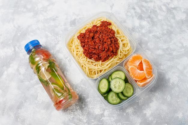 Spaghetti alla bolognese da asporto in una scatola da pranzo in plastica con bevanda disintossicante e fetta di frutta sulla luce Foto Gratuite