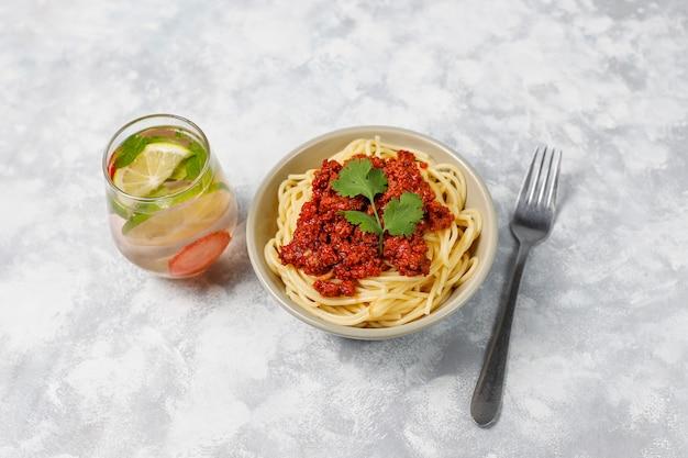 Spaghetti alla bolognese e limonata su cemento grigio Foto Gratuite