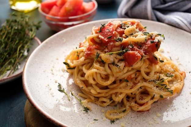 Spaghetti con pomodori e timo in un piatto su un tavolo blu Foto Premium