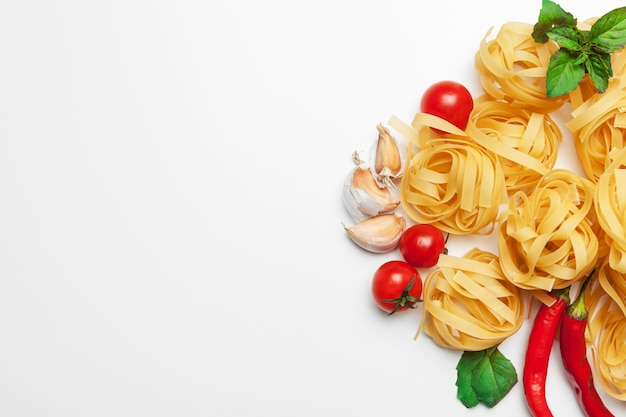 Spaghetti della pasta con gli ingredienti per la cottura della pasta su un fondo bianco, vista superiore. Foto Premium