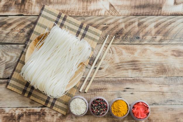 Spaghetti di riso crudo con le bacchette e ciotole di spezie secche sul tavolo Foto Gratuite