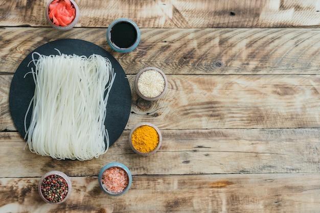 Spaghetti di riso su roccia tondeggiante di ardesia circondata da pepe in grani; curcuma; riso; salsa e zenzero sottaceto Foto Gratuite