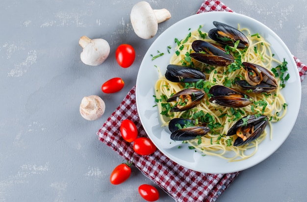 Spaghetti e cozze con pomodori, funghi in un piatto su intonaco e asciugamano da cucina Foto Gratuite