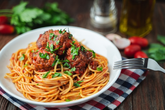 Spaghetti e polpette con salsa di pomodoro in piatto bianco sul bordo rustico in legno Foto Premium