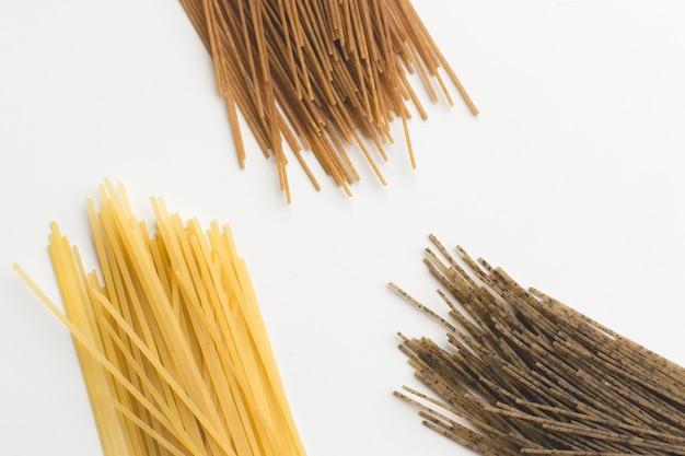 Spaghetti interi della pasta tricolora su una priorità bassa bianca Foto Gratuite