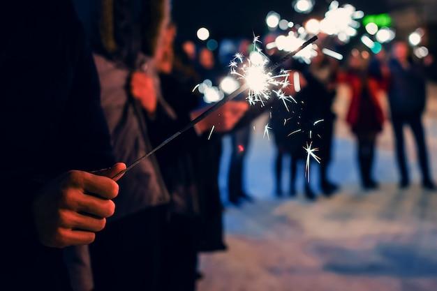Sparkler nelle mani di persone in vacanza con scintille Foto Premium