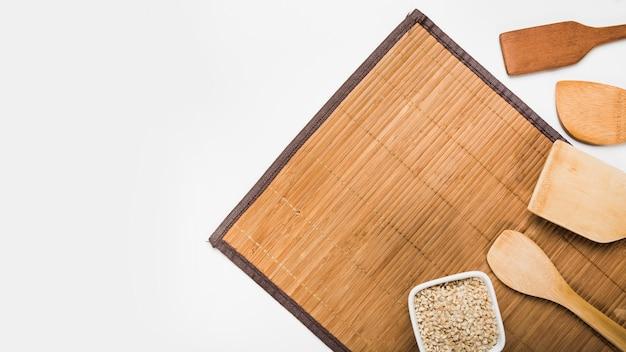 Spatole in legno e ciotola di riso integrale crudo su placemat su sfondo bianco Foto Gratuite