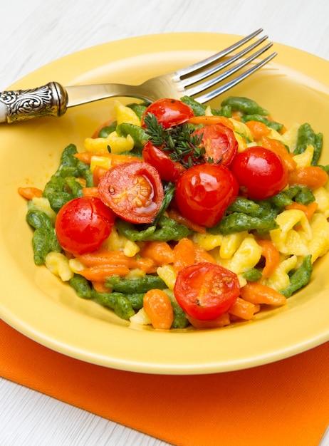 Spatzle colorato sul piatto giallo Foto Premium