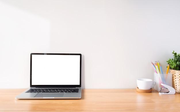 Spazio di lavoro e laptop con schermo bianco. Foto Premium