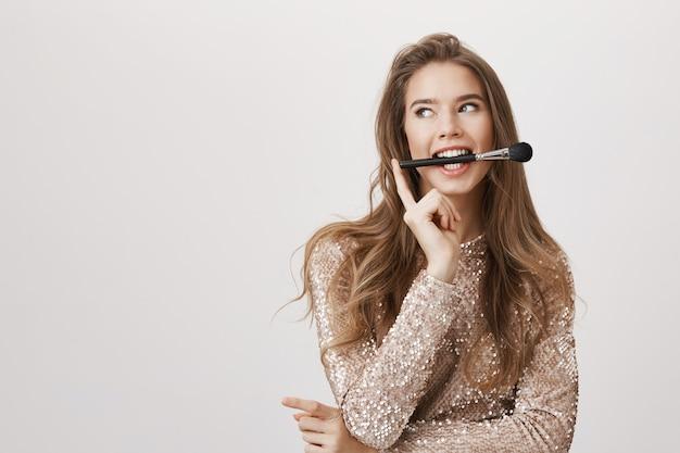 Spazzola attraente della stretta della donna in bocca, distoglie lo sguardo Foto Gratuite