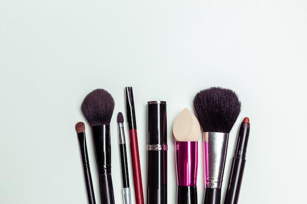 Spazzola e cosmetici isolati su uno sfondo bianco. vista dall'alto. Foto Premium