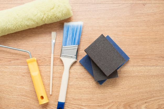 Spazzole e rulli di pittura su fondo di legno. strumenti di costruzione per la verniciatura di superfici Foto Premium