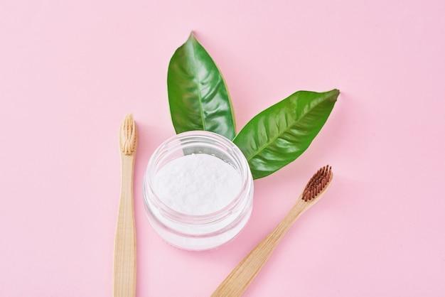 Spazzolini da denti in legno di bambù con bicarbonato di sodio in barattolo di vetro e foglie verdi su una superficie rosa. denti salute e mantenere il concetto di bocca Foto Premium