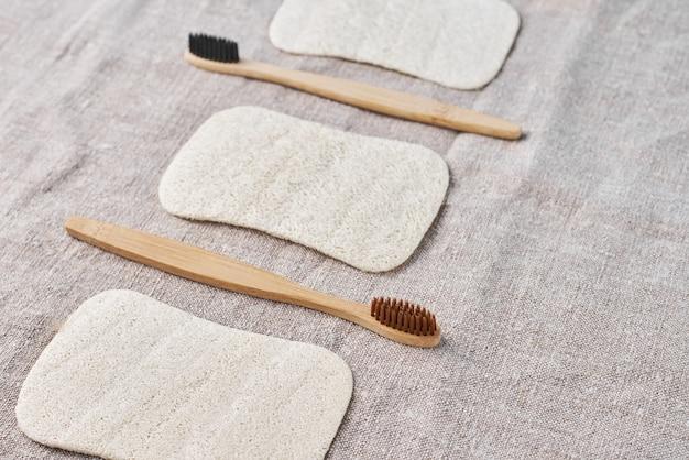 Spazzolini da denti in legno e lavamani naturali su tela grigia, vista dall'alto Foto Premium