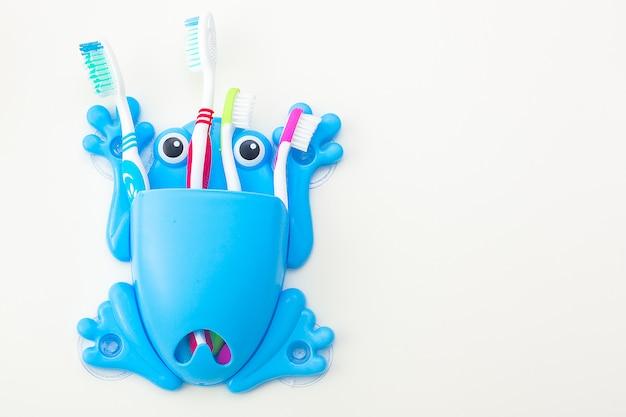 Spazzolini da denti su sfondo neutro. concetto di igiene familiare. Foto Premium