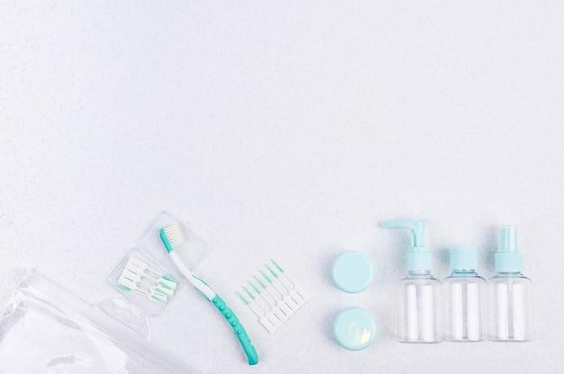 Spazzolino da denti e contenitori di plastica per il viaggio su uno sfondo bianco e le bacchette. disteso Foto Premium