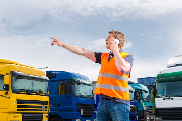 Spedizioniere davanti a camion su un deposito Foto Premium