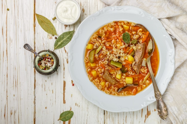 Spessa zuppa di sottaceti con manzo, verdure (sottaceti, carote, cipolle, patate, pomodori) e orzo perlato Foto Premium