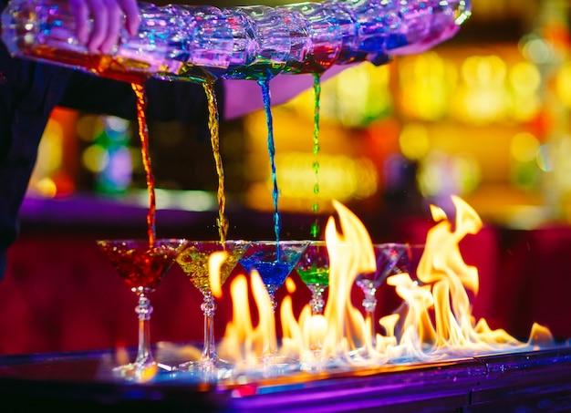 Spettacolo di barman. il barista versa cocktail alcolici. Foto Premium