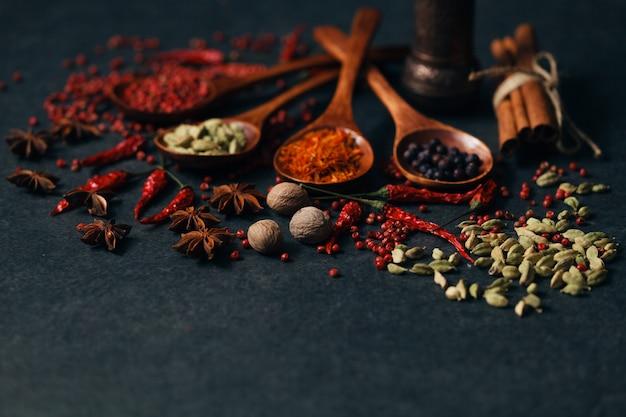 Spezie aromatiche in cucchiai di legno sul tavolo di pietra scura Foto Premium