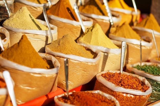 Spezie colorate in sacchetti in un mercato di goa Foto Premium