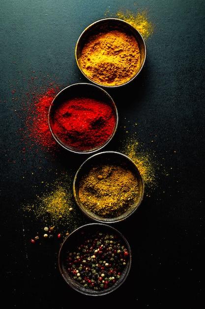 Spezie colorate sul tavolo scuro Foto Gratuite