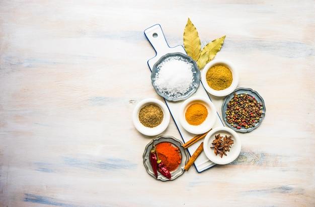 Spezie differenti sulla tavola di legno bianca Foto Premium