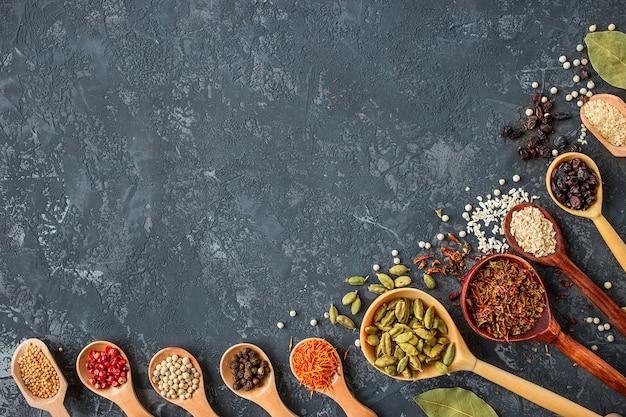 Spezie ed erbe aromatiche su pietra nera, flat lay. Foto Premium