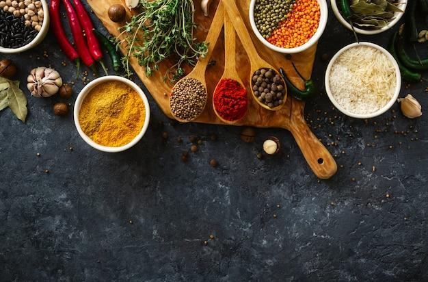 Spezie, erbe, riso e vari fagioli e condimenti per la cottura sul backgraund scuro con copyspace vista dall'alto Foto Premium