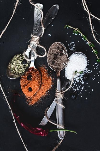 Spezie in diversi cucchiai sul tavolo di pietra di marmo. tonalità rustica dai colori vintage Foto Premium