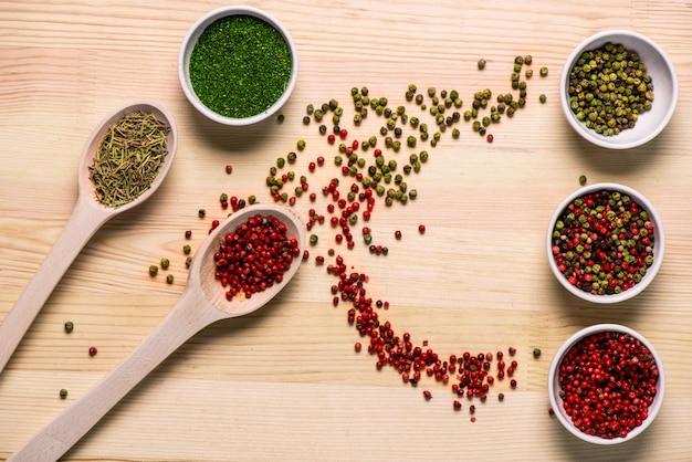 Spezie in piatti e cucchiai sulla tavola di legno Foto Gratuite