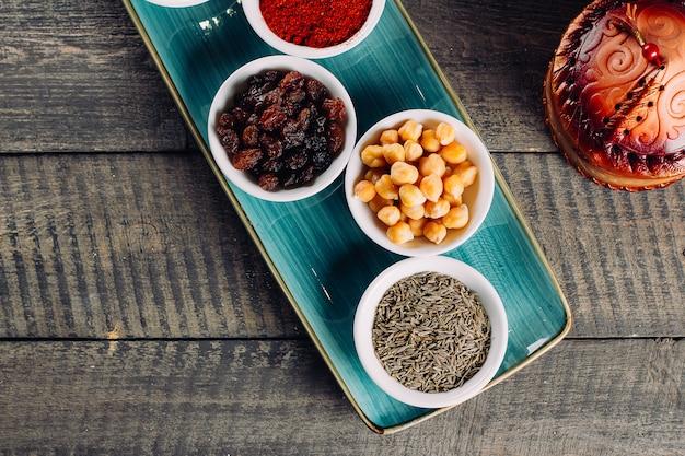 Spezie in piccole ciotole bianche su fondo di legno marrone Foto Premium