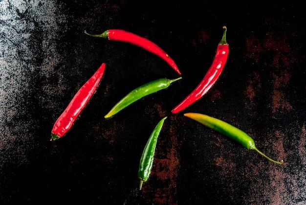 Spezie per cucinare. peperoncini rossi e verdi piccanti sul fondo arrugginito del vecchio metallo Foto Premium