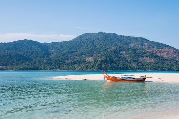Spiaggia di sabbia bianca con barca a coda lunga in legno in mare tropicale Foto Premium